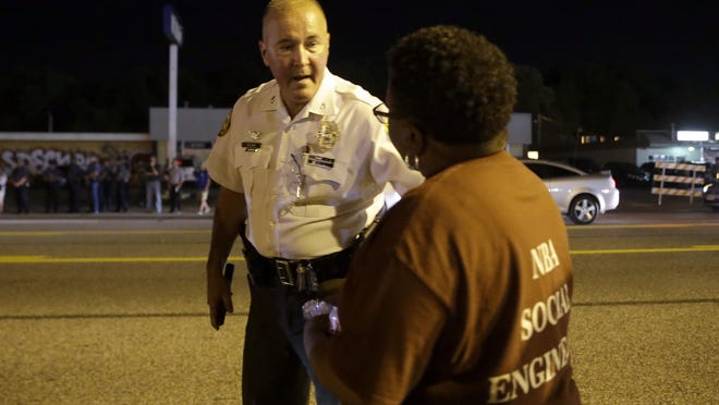 """St. Louis County Police Chief Jon Belmar talks to a protester as people gather along West Florissant Avenue in Ferguson, Mo., Tuesday. The St. Louis suburb has seen demonstrations for days marking the anniversary of the death of 18-year-old Michael Brown, whose shooting death by a Ferguson police officer sparked a national """"Black Lives Matter"""" movement. Tuesday was the fifth consecutive night a crowd gathered on West Florissant."""