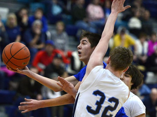Havre's Dane Warp shoots as Great Falls High's Brendan Howard defends in a game last season. The Bison-Blue Pony rivalry dates back to 1930.
