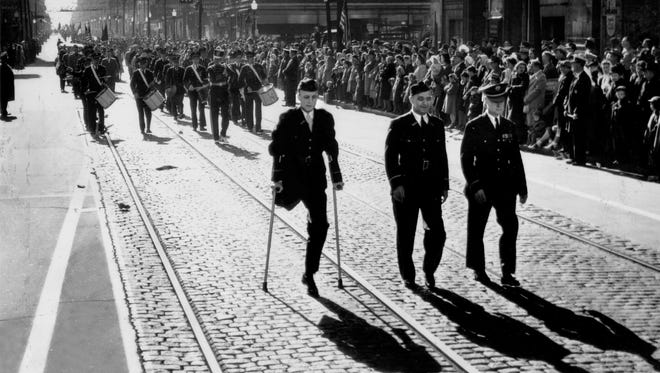 NOVEMBER 11, 1948: Armistice Day Parade, Main and Court Streets, downtown Cincinnati, Ohio. Despite losing his leg on a warship, William N. Morton proudly marches on the 30th anniversary of the end of World War I.