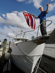 "Dave Cooper holds the Hawaiian flag atop his ship ""Swan"