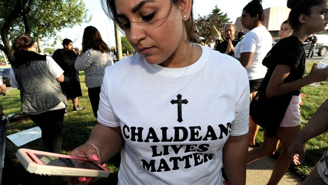 Astevana Shaya, 28, of Sterling Heights, wears a Chaldeans Lives Matter T-shirt at a protest on June 12, 2017, after an immigration crackdown that they say could send Iraqi Christians back to a country where they face persecution. On the back is a portrait of her brother, Aysar Shaya, 39, who is being detained.