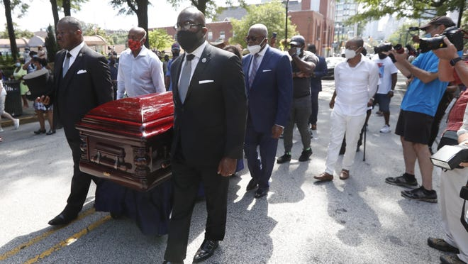 Mourners march with the casket of the Rev. C.T. Vivian to the Martin Luther King Jr. National Historical Park during a memorial service Wednesday in Atlanta.