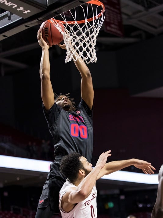 SMU's Ben Moore (00) goes up for a shot over Temple's Obi Enechionyia (0) during the first half of an NCAA college basketball game, Thursday, Feb. 9, 2017, in Philadelphia. (AP Photo/Chris Szagola)