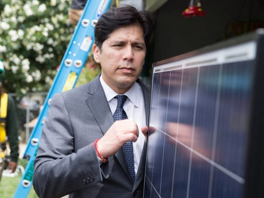 State Senate leader Kevin de León studies panels at a solar installation project.