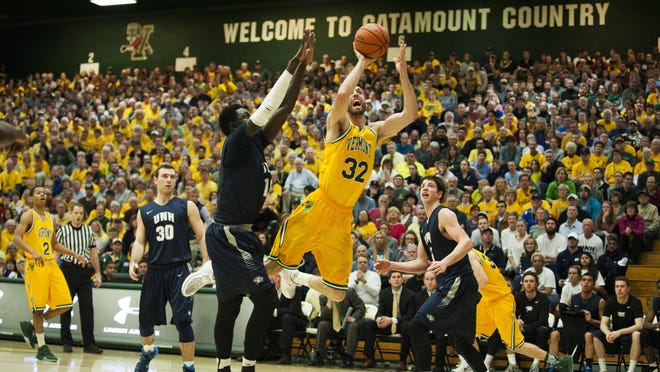 Catamounts forward Ethan O'Day (32) leaps past Wildcats forward Iba Camara (10) for a layup during the America East men's basketball semifinal game at Patrick Gym on Monday night.