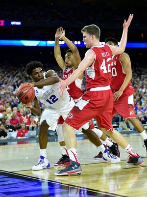 Duke Blue Devils forward Justise Winslow (12) is defended by Utah Utes forward Jakob Poeltl (42) and guard Brandon Taylor (11) and forward Chris Reyes (20) during the first half in the semifinals of the south regional of the 2015 NCAA tournament at Reliant Stadium.