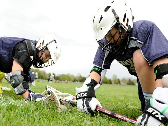 Ten year-olds Owen Kirkham and Josh Hays practice facing off during a Granville Youth Lacrosse practice on Tuesday, May 3, 2016 on the lawns in front of Bryn Du Mansion.