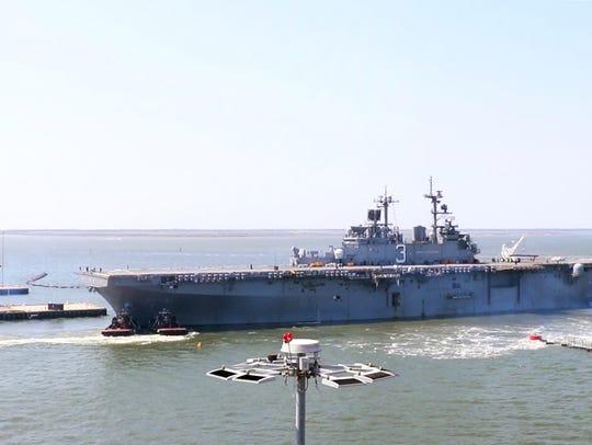 The USS Kearsarge, an amphibious assault ship, pulling