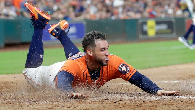 Houston Astros' George Springer slides across home plate to score on a single by Josh Reddick during the third inning of the team's baseball game against the Minnesota Twins on Friday, July 14, 2017, in Houston.