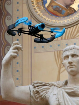 "CNN signed a partnership agreement with the FAA to advance research on drones as a news-gathering tool. In this photo, the new Bebop Parrot drone flies front of a Rome marble statue ""August en Triomphateur"" in a demo presentation. (AP Photo/Francois Mori) ORG XMIT: XFM115"