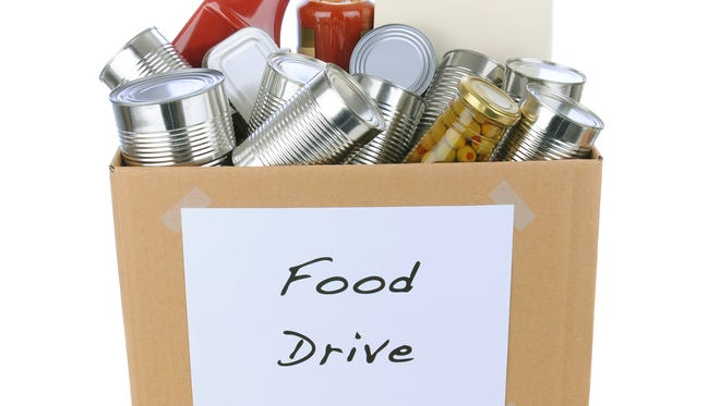 A box full of canned and packaged foodstuff for a charity food donation drive.