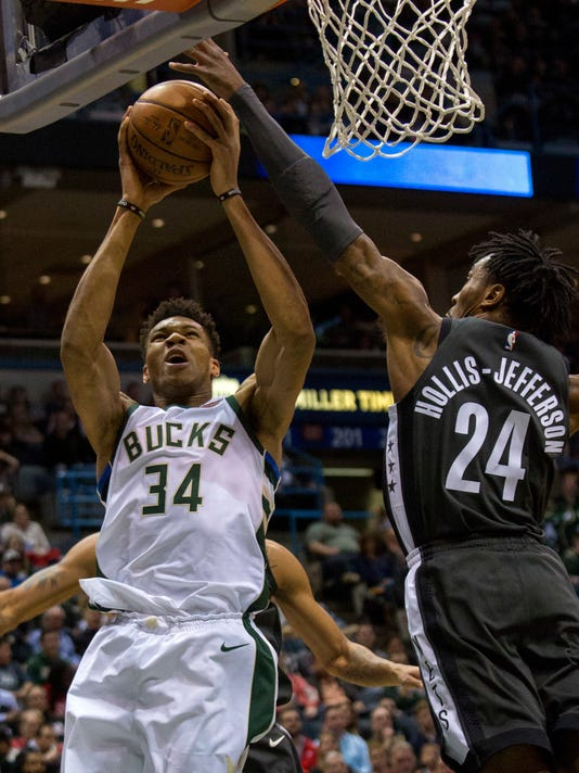 Milwaukee Bucks forward Giannis Antetokounmpo, left, is defended by Brooklyn Nets forward Rondae Hollis-Jefferson as he drives to the basket during the first half of an NBA basketball game Thursday, April 5, 2018, in Milwaukee. (AP Photo/Darren Hauck)