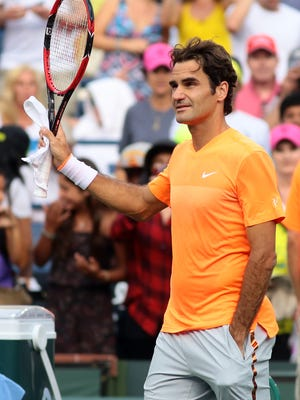 Roger Federer waves his racquet to the crowd after defeating Diego Schwartzman of Argentina in a second-round match on Sunday at the BNP Paribas Open in Indian Wells. Federer won in straight sets 6-4, 6-2.
