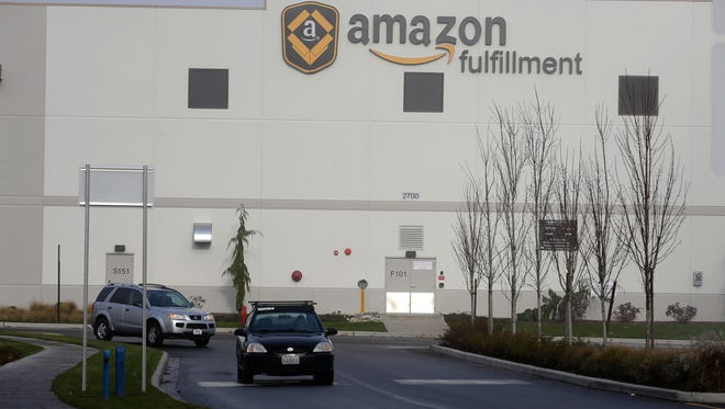 FILE - In this Nov. 30, 2015 file photo, cars drive away from Amazon.com's fulfillment center in DuPont, Wash. Buying things online could soon get pricier for many people after the U.S. Supreme Court's decision Monday, Dec. 12, 2016 not to get involved in a case that may lead to states collecting billions in lost sales taxes. The court opted not to hear a challenge to a Colorado law requiring internet retailers to notify customers and the state how much they owe in Colorado taxes. (AP Photo/Ted S. Warren, file)