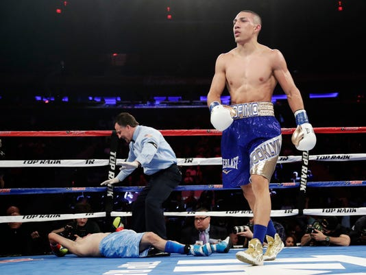 Teofimo Lopez, right, reacts after knocking down Ronald Rivas during the second round of a lightweight boxing match Saturday, May 20, 2017, in New York. Lopez stopped Rivas in the second round. (AP Photo/Frank Franklin II)