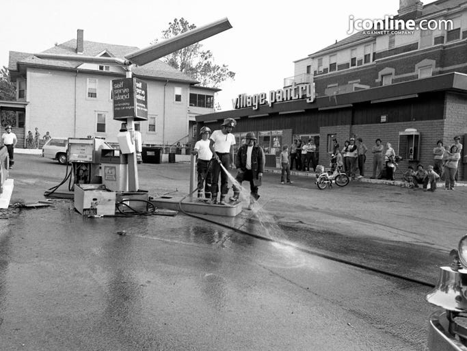 Lafayette Fire Department firefighter Bob Burke washes away spilled gas to avoid a fire at Village Pantry, 6 S. Ninth St. Jeffrey L. Strugeon told the Lafayette Police Department he knocked over two of the store's gas pumps after a broken clutch in his truck caused him to hit the pumps. Photo taken June 9, 1984.