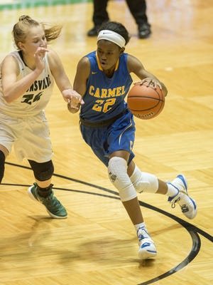 Carmel High School senior Tomi Taiwo (22) drives the ball past the defense of Zionsville High School junior Maddie Nolan (24) during the second half of the championship game of the Girls' Hall of Fame Classic tournament, Friday, December 29, 2017, at New Castle High School. Carmel won 75-51.