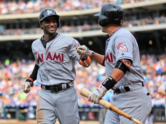 Miami Marlins' Adeiny Hechavarria, left, is greeted by Martin Prado after scoring on a single hit by Tom Koehler during the second inning of the baseball game against the New York Mets, Monday, July 4, 2016 in New York. (AP Photo/Seth Wenig)