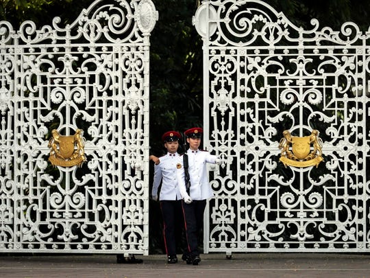 Singapore military personnel patrol in front of the gate of the Istana Presidential Palace.