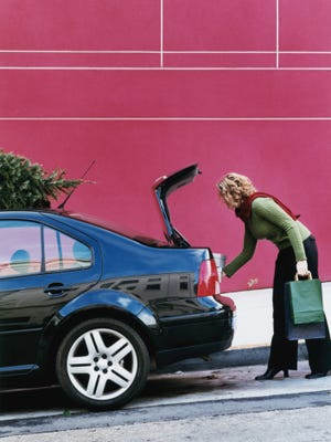 Woman loading packages into trunk of car, Christmas tree on car roof