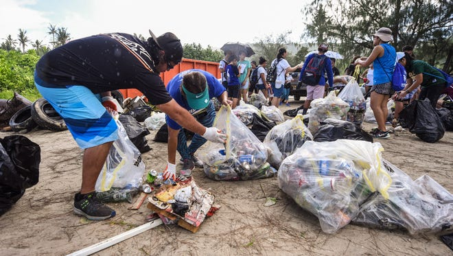 Couple, Peter Manglona, left, and Arlene Pestanas separate bags of trash they and other volunteers collected during the 23rd Annual Guam International Coastal Cleanup 2017 at Tanguisson Beach on Saturday, Sept. 16, 2017.