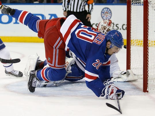 New York Rangers left wing Chris Kreider (20) flies in front of Montreal Canadiens goalie Dustin Tokarski (35) as the puck sails past the far post during the second period of Game 3 of the NHL hockey Stanley Cup playoffs Eastern Conference finals, Thursday, May 22, 2014, in New York. (AP Photo/Kathy Willens)
