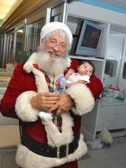 """""""Santa"""" Dan Sutter holds one-month-old Jacob Reynoso, who spent his first Christmas at Golisano Children's Hospital."""