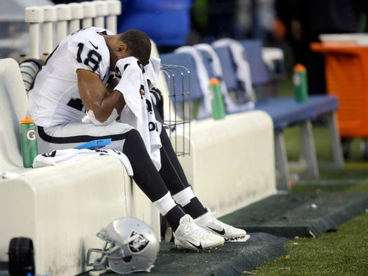 Oakland Raiders wide receiver Andre Holmes sits on the bench late in the fourth quarter of an NFL football game against the Seattle Seahawks, Sunday, Nov. 2, 2014, in Seattle. The Seahawks beat the Raiders 30-24. (AP Photo/Stephen Brashear)