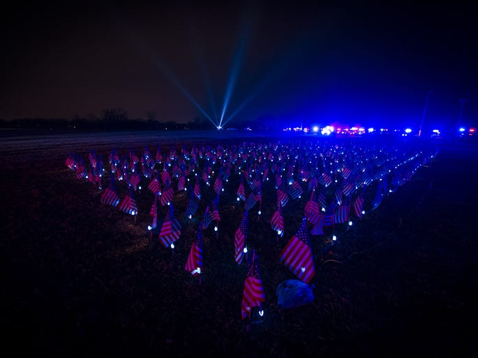 A field of flags represent each of the fallen officers that have died in the line of duty in Indiana. Supports of family and friends of fallen Indiana law enforcement officers gathered Tuesday, December 3, 2013, at the Indiana Law Enforcement Academy in Plainfield for the 16th Annual Project Blue Light memorial ceremony.