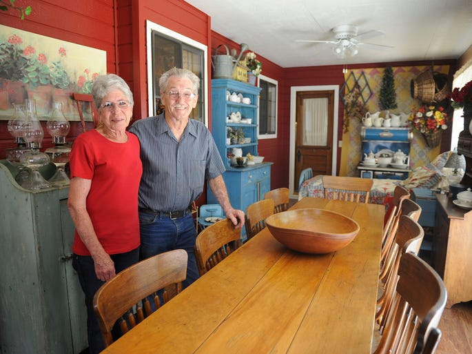 Sharon and Bobby Cheek stand in a back porch that was converted to a extra room, complete with a quilt-covered twin bed at one end for nap time after a meal. Country decorating is all about down-home comfort, they said.