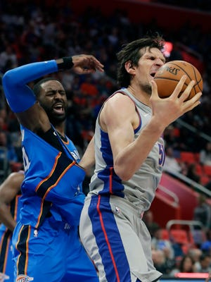 Pistons center Boban Marjanovic, right, and Thunder forward Patrick Patterson react as Marjanovic recovers a rebound but has his left arm stuck in Patterson's jersey during the first half on Saturday, Jan. 27, at Little Caesars Arena.