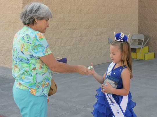 A resident hands over a cash donation to Valentina