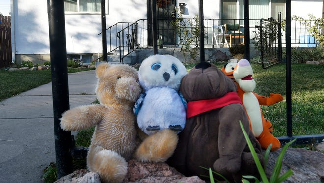 Stuffed animals are placed by mourners in front of a home in central Colorado Springs, Colorado, on Oct. 17, 2017. Police arrested a 19-year-old man in the stabbing deaths of his young brother and sister and an attack on his father in their Colorado home.