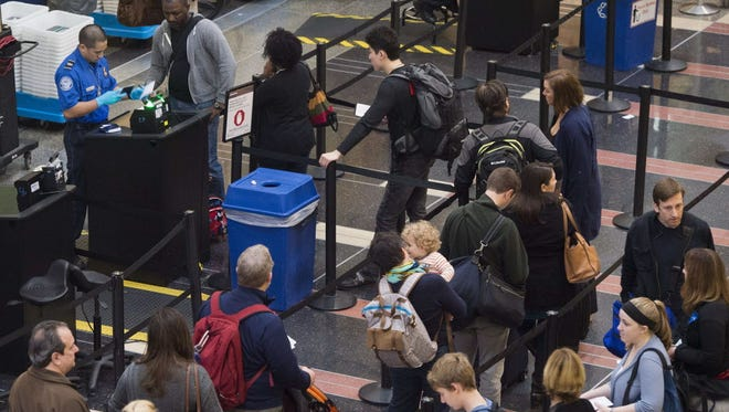 Passengers stand in line to go through a Transportation Securitiy Administration checkpoint Dec. 23, 2015, at Reagan National Airport in Arlington, Virginia.