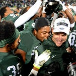 Head coach Mark Dantonio smiles as he is embraced by players Craig Evans (72) and Arjen Colquhoun (36) after MSU's 55-16 win over Penn State Saturday, November 28, 2015, at Spartan Stadium in East Lansing.