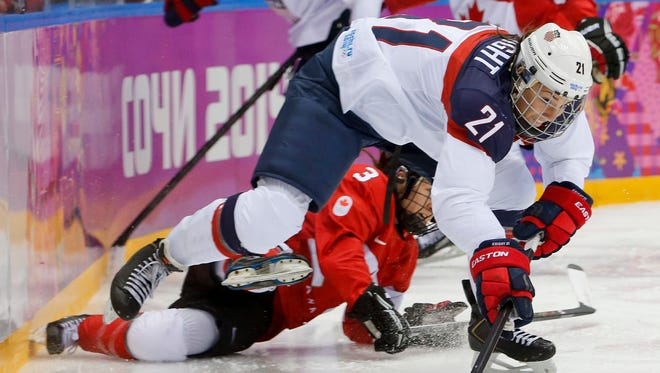 The United States' Hilary Knight (21) passes the puck against Canada on Feb. 20, 2014.