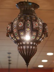 A Moroccan lamp hangs from the center of the dining