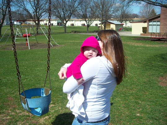 "Ann Harris (not her real name), shown here playing with her 7-month-old daughter at Optimist Park Playground, is building a new life for herself in Lebanon after being victimized by Luzerne County Judge Mark A. Ciavarella's ""Kids for Cash"" scheme."