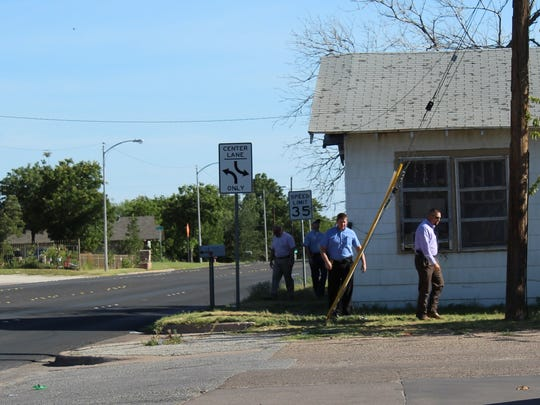 Abilene Police Department detectives walk the area