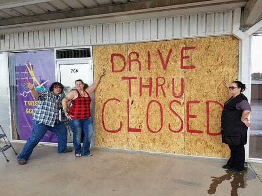 Twister Scissor owner Betzi Torres and employees stand in front of the salon window they boarded up. A 2009 Ford Sport Utility Vehicle crashed through the building Friday.