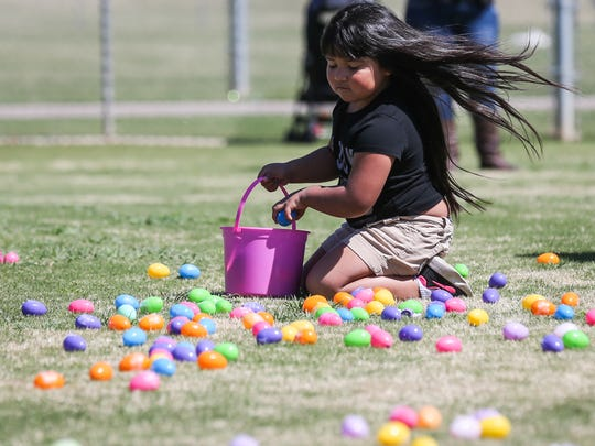 A child picks up eggs during Easter Fest Saturday, March 31, 2018, at Texas Bank Sports Complex.