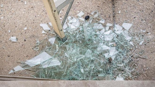 Shards of glass lie on the sidewalk in front of the Boost Mobile store Monday, June 1, 2020 on Gale Avenue in Peoria after alleged looters broke in overnight.