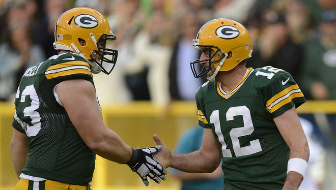 Green Bay Packers quarterback Aaron Rodgers and Corey Linsley congratulate each other after the Packers scored on a 80-yard touchdown reception against the New York Jets.