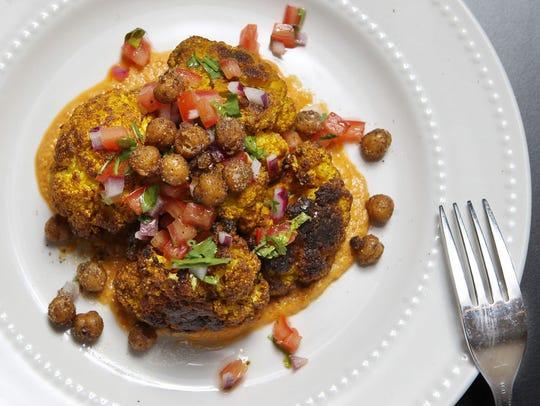 An entree of roasted curried cauliflower, hummus, pico