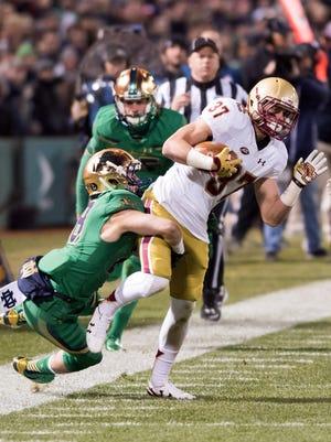 Notre Dame Fighting Irish defensive back Nicco Fertitta (28) attempts to tackle Boston College Eagles kick returner Michael Walker (37), a Naples High School graduate, in the third quarter at Fenway Park. Notre Dame won 19-16 on Saturday, Nov. 21, 2015.