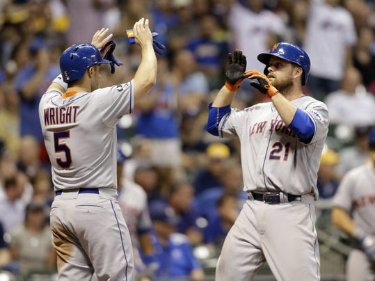 New York Mets' Lucas Duda (21) gets high-fives from David Wright (5) after Duda's two-run home run against the Milwaukee Brewers during the ninth inning of a baseball game Friday, July 25, 2014, in Milwaukee. (AP Photo/Jeffrey Phelps)