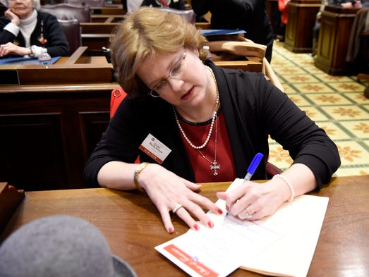 Beth Clayton Amos signs documents as Tennessee's electors
