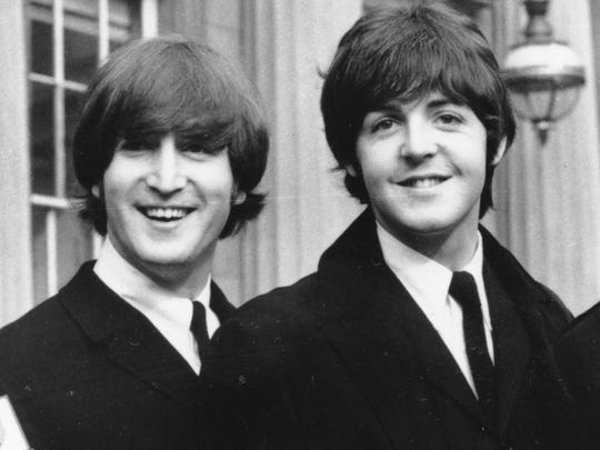 This Oct. 26, 1965 file photo shows John Lennon, left, and Paul McCartney as they smile during a ceremony at Buckingham Palace in London.