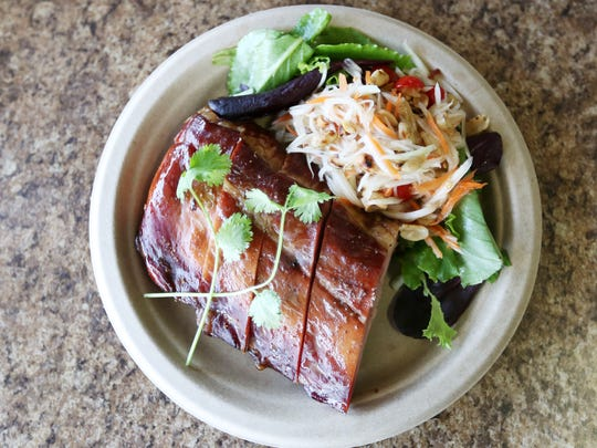 Smoked Baby Back Ribs with a side Papaya Salad ($12) is served at Big Blue Thai BBQ food truck on South Commercial.