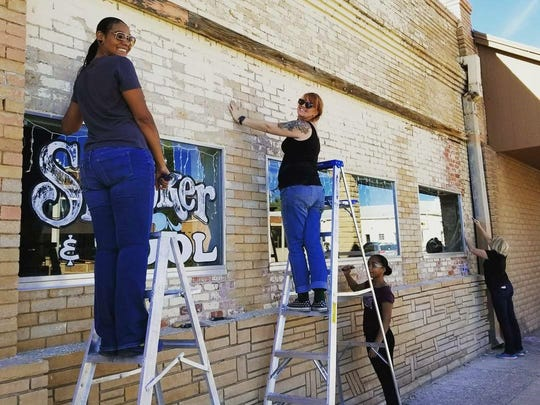 Volunteers work on the facade of Mission Billiards during the project.